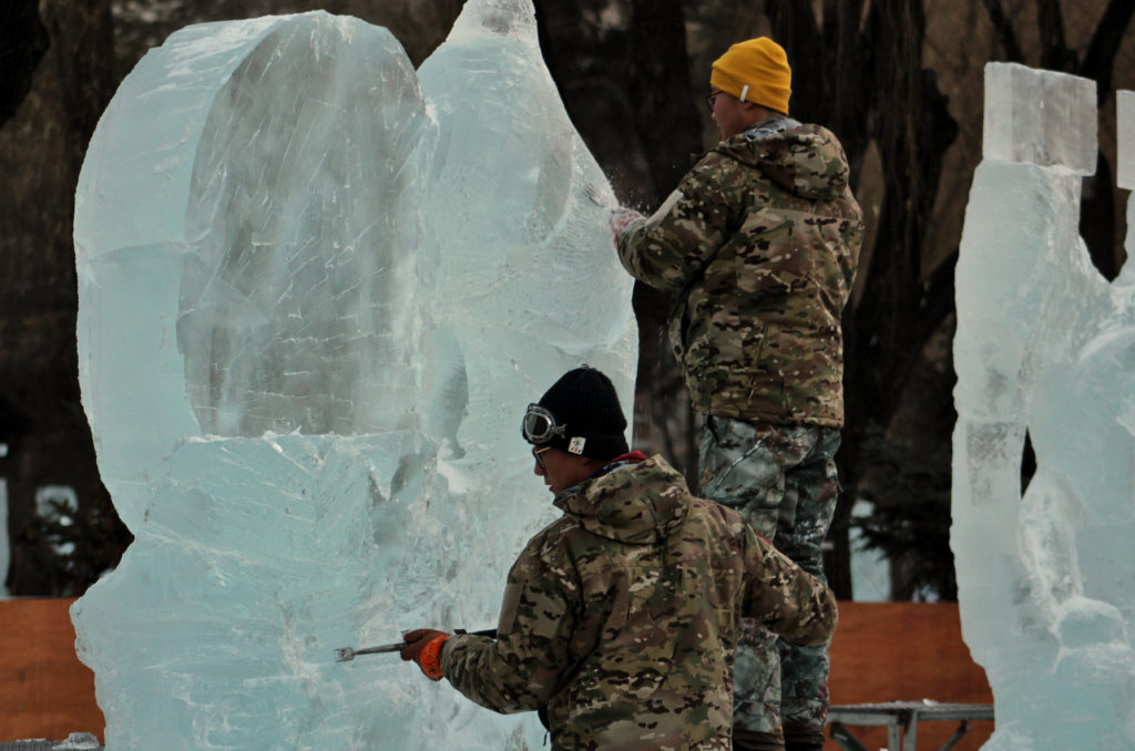 Two men working on carving an ice sculpture