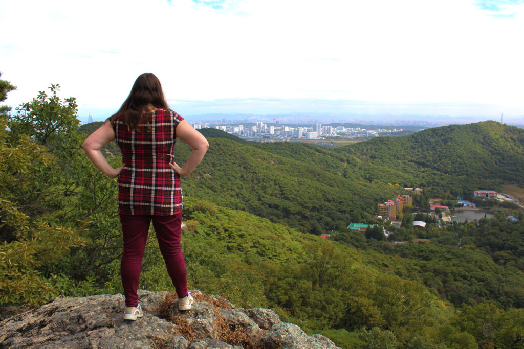 Photo of myself standing on a rock overlooking the view of Pyongyang in the distance