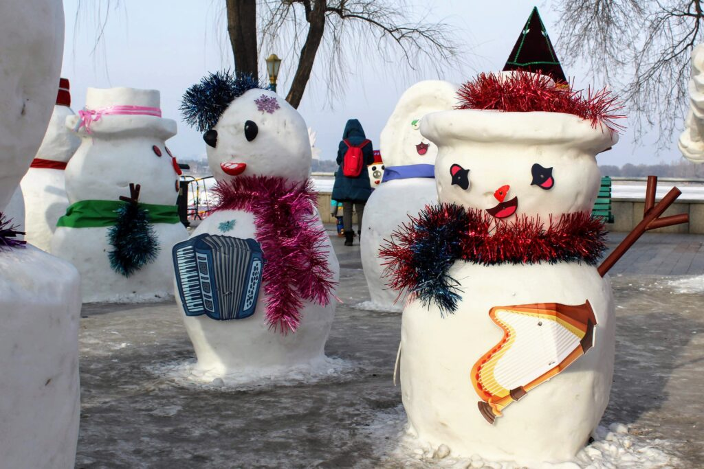 Two snowmen holding paper instruments