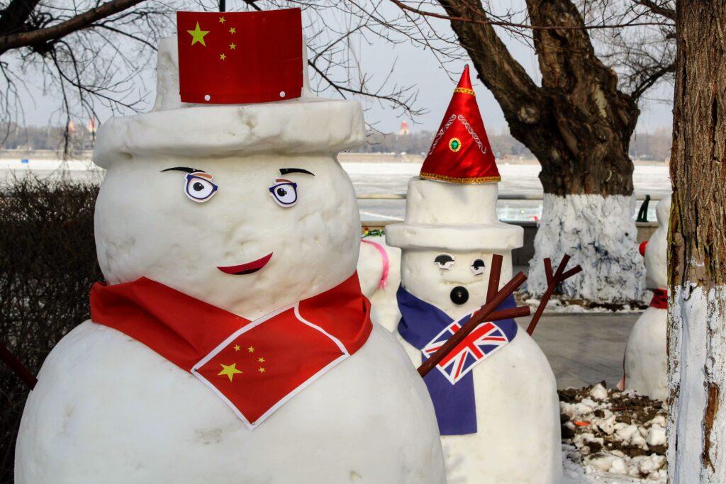 Two snowmen wearing flags.